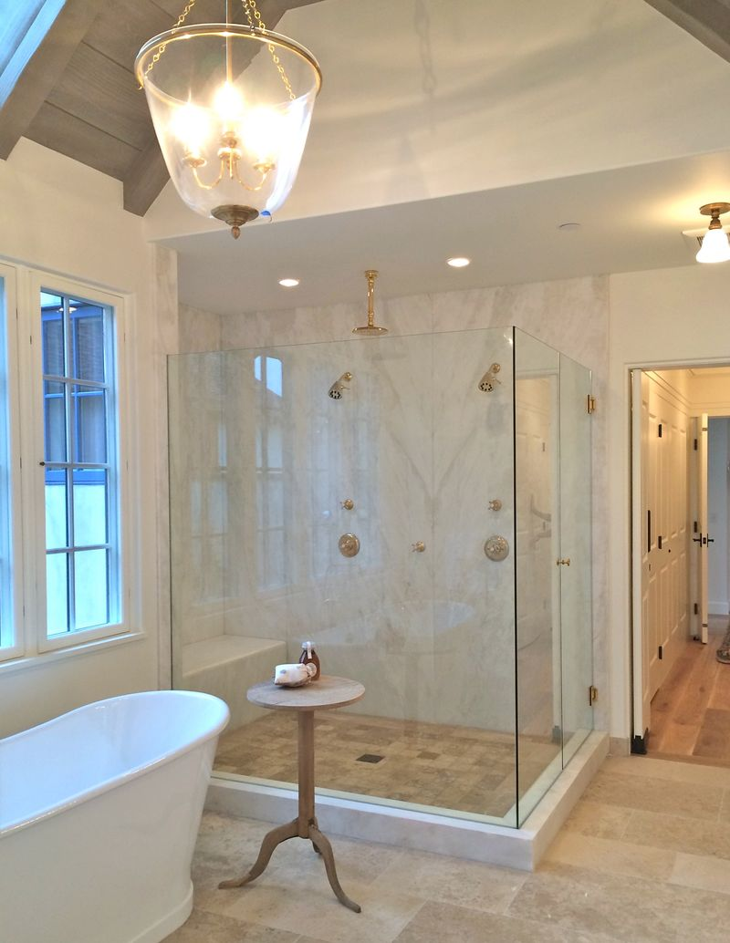 Beautiful bathroom with stone flooring and glass shower walls - Giannetti Home.