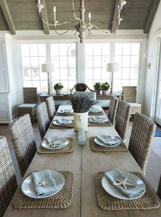 Rattan dining chairs at farmhouse table in a kitchen by Giannetti Home. See more rustic elegant French farmhouse design ideas and decor inspiration. #frenchfarmhouse #interiordesign #frenchcountry