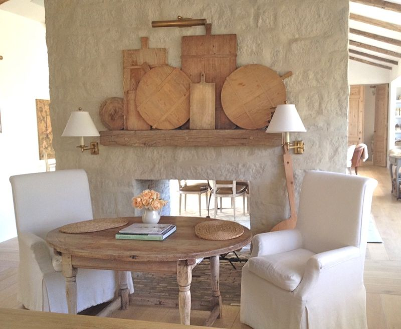 Patina Farm breakfast dining area next to limestone fireplace in French farmhouse kitchen.