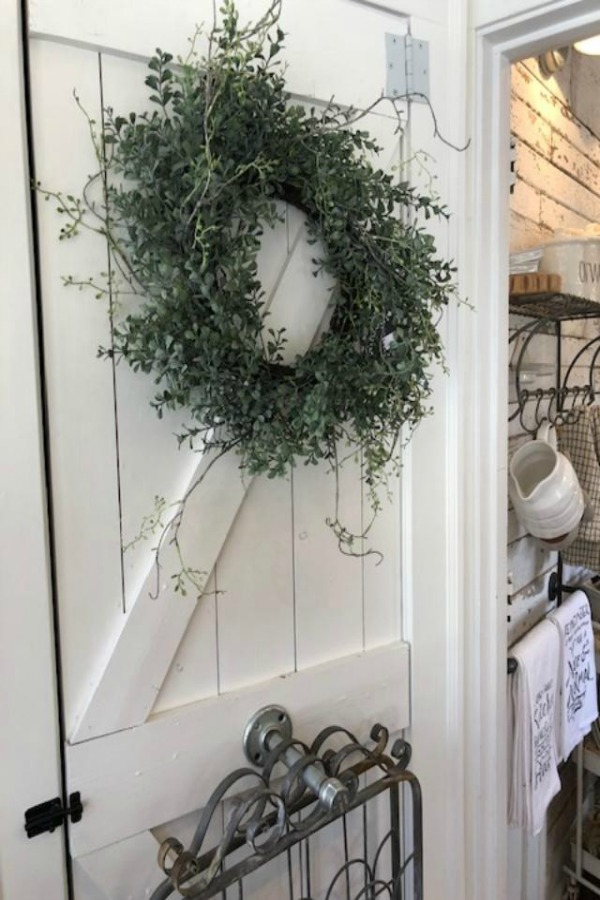 White barn door hung with wreath and garden gate wall decor at Urban Farmgirl. Photo by Hello Lovely Studio.
