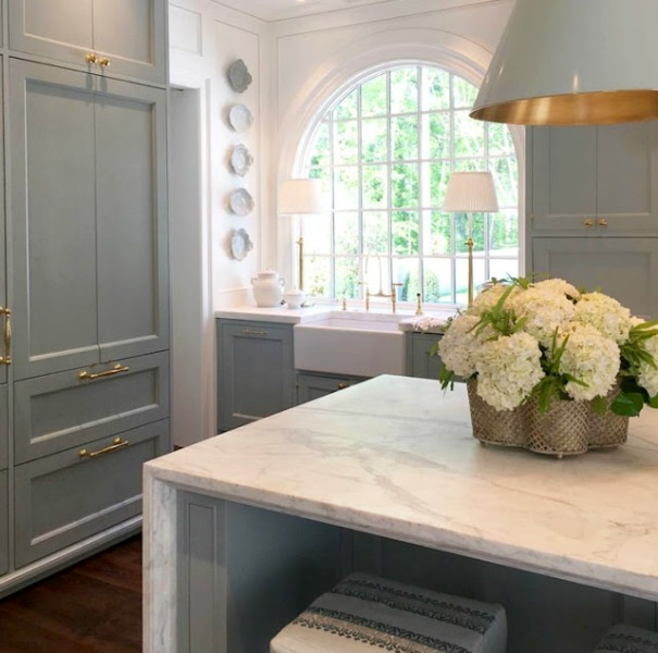 Elegant and luxurious kitchen with Farrow & Ball Light Blue cabinets, Sherwin Williams Alabaster on walls, and design by Design Galleria and Lauren DeLoach. Come explore Interior Designers Favorite White Paint Colors for ideas, photos, and inspiration.