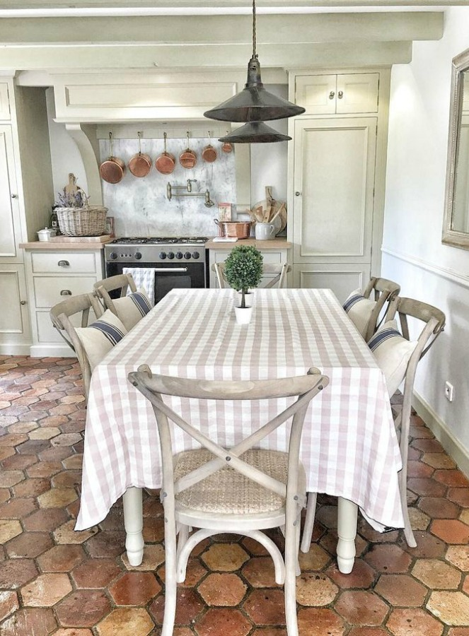 Terracotta hexagon tiles on kitchen floor in French farmhouse by Vivi et Margot. Pale and Lovely European Country White Interiors to Inspire with photo gallery.#frenchfarmhouse #interiordesign #frenchcountry