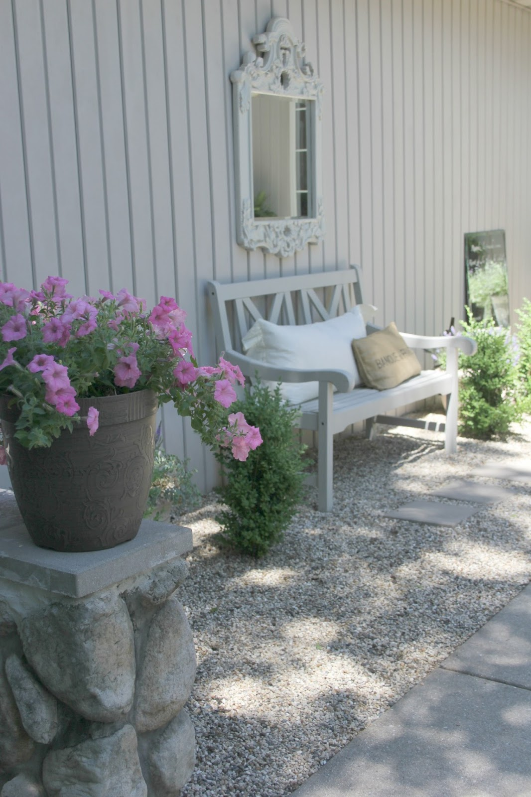 My French courtyard garden with pea gravel, bench, and pink flowers - Hello Lovely Studio.