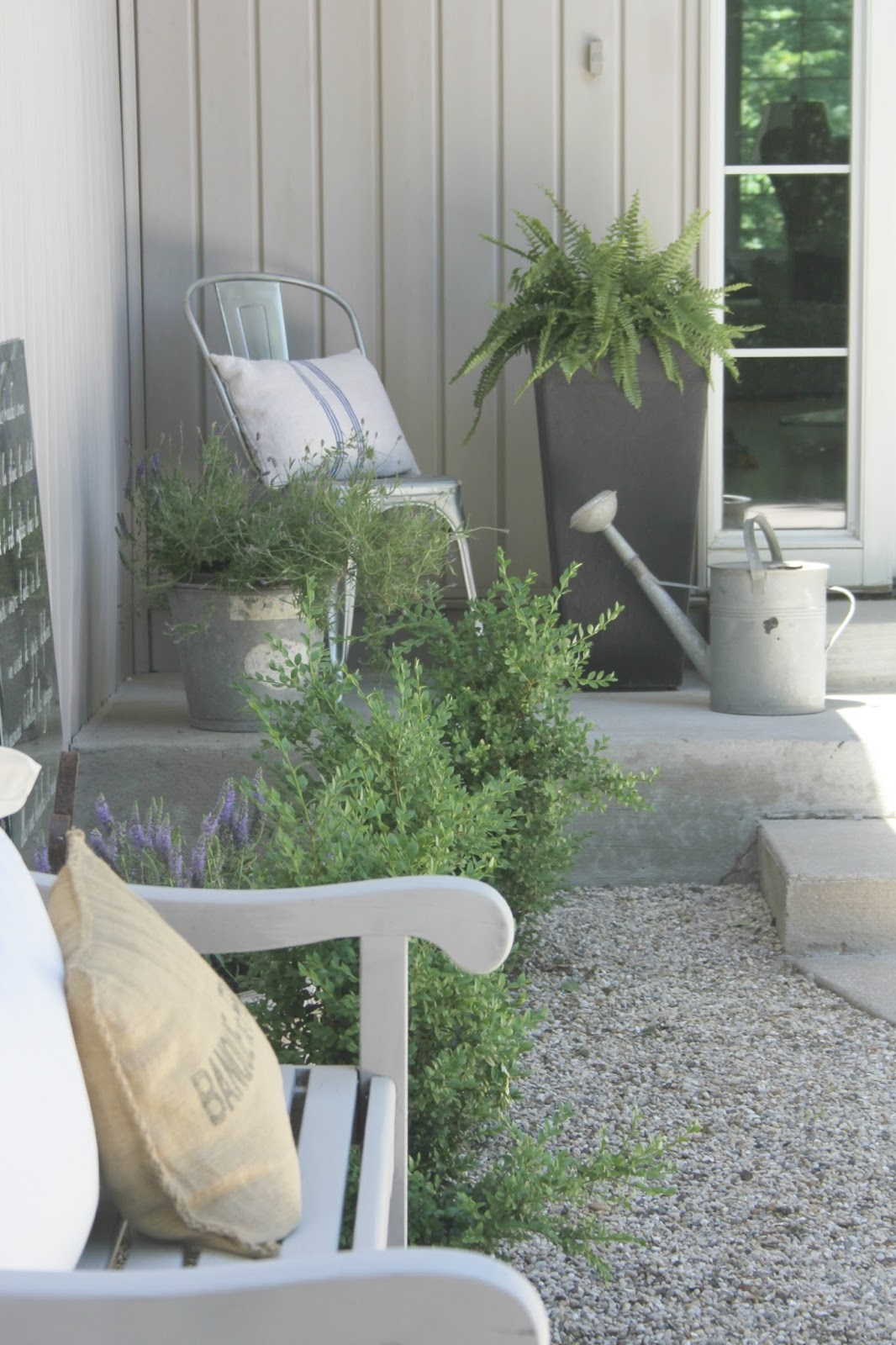 Pea gravel, boxwood, and bench with French farmhouse pillows in French country courtyard - Hello Lovely Studio.