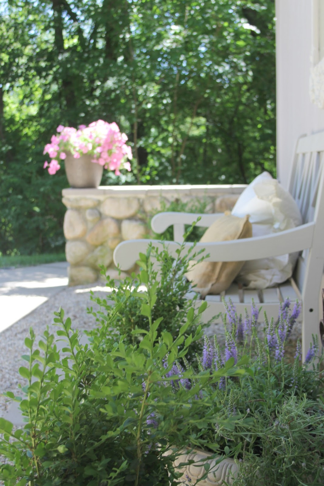 French country courtyard with beautiful bench, blue blooms, and stone wall - Hello Lovely Studio.