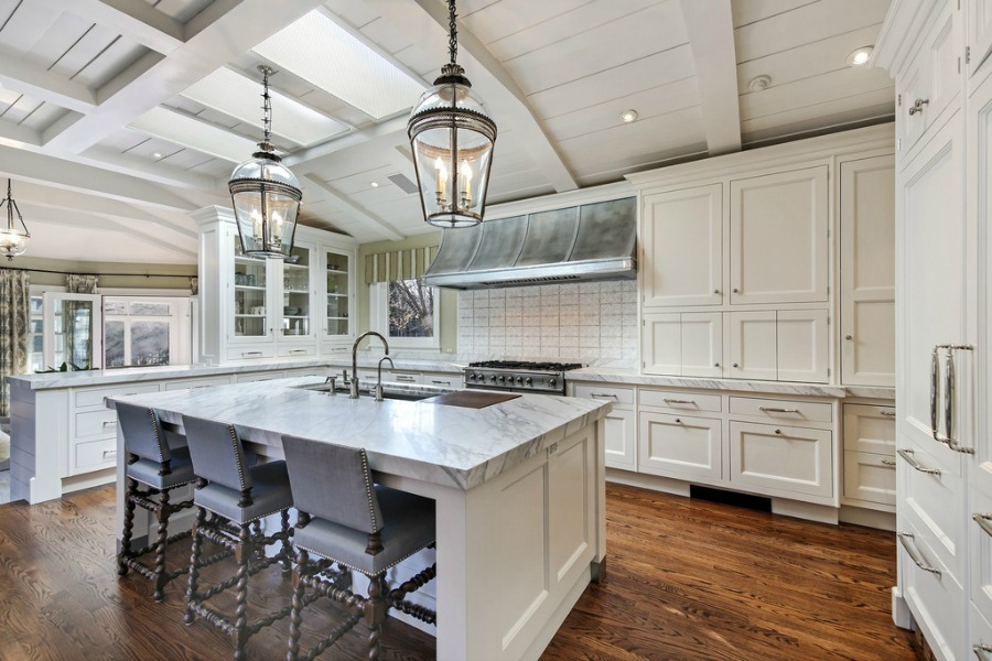 Luxurious classic white coastal kitchen with marble countertops and Shaker cabinetry.