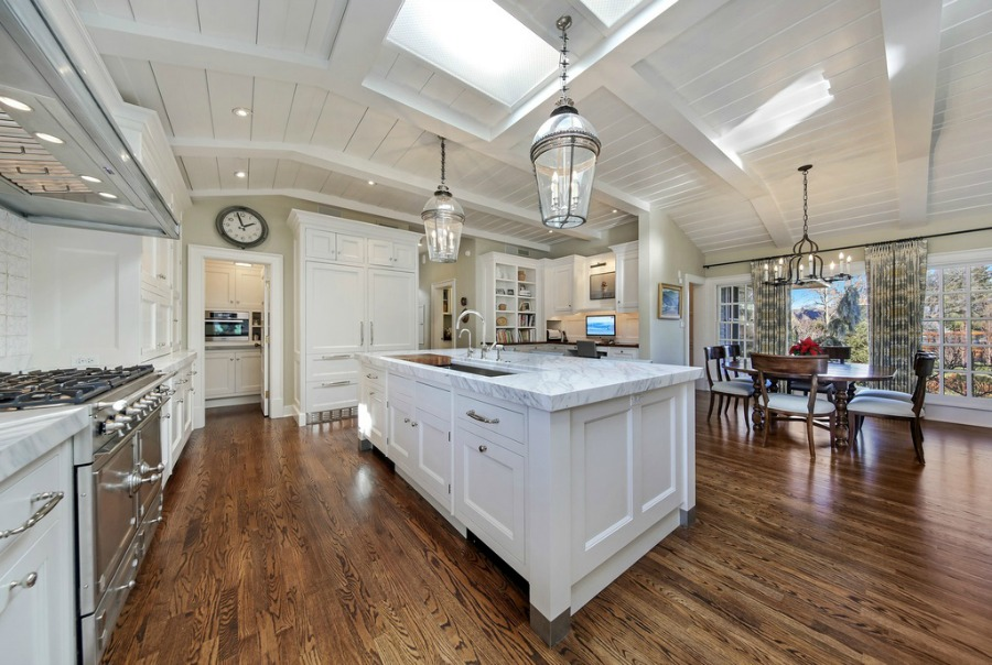 Classic and coastal style in a luxurious kitchen with dark hardwood floors and white cabinets.