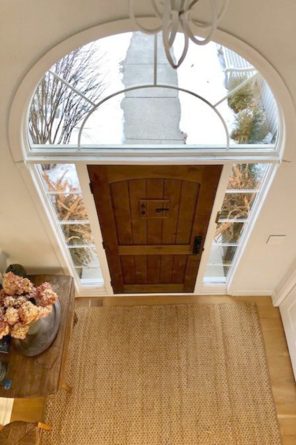 Rustic alder front door in an entry with jute area rug. Hello Lovely Studio. Walls are painted Benjamin Moore White.