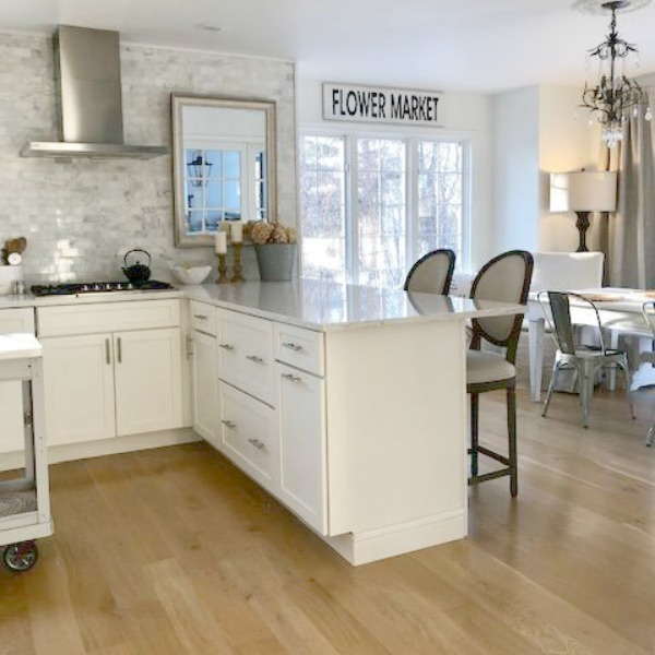 White classic kitchen with coastal modern farmhouse style and European country influence. Wall paint is Benjamin Moore White.