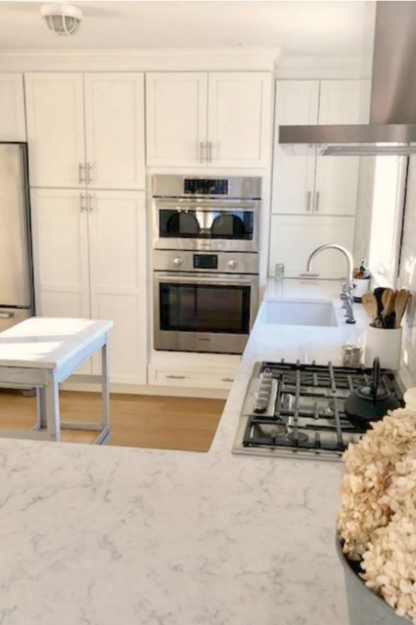 My classic white kitchen with industrial steel cart, marble backsplash, and Shaker cabinets. Hello Lovely Studio.