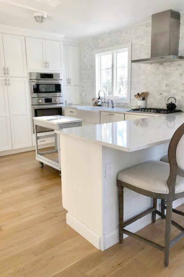 White Shaker style kitchen cabinets, farm sink, and carrara marble subway tile wall - Hello Lovely Studio.