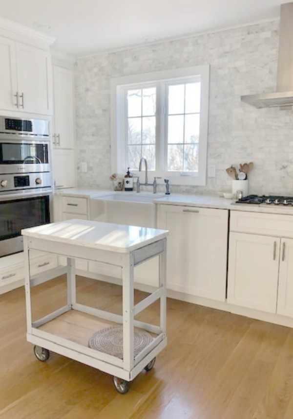 Classic white coastal style kitchen with polished marble backsplash statement wall, Shaker cabinets, industrial work table, and Viatera quartz (Minuet). Hello Lovely Studio.