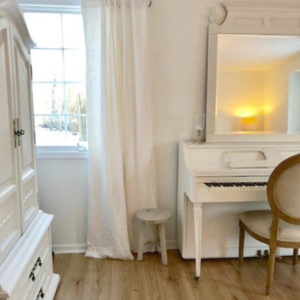 French Nordic style and shabby chic decor in a studio with white vintage piano and walls painted Benjamin Moore White. Hello Lovely Studio.