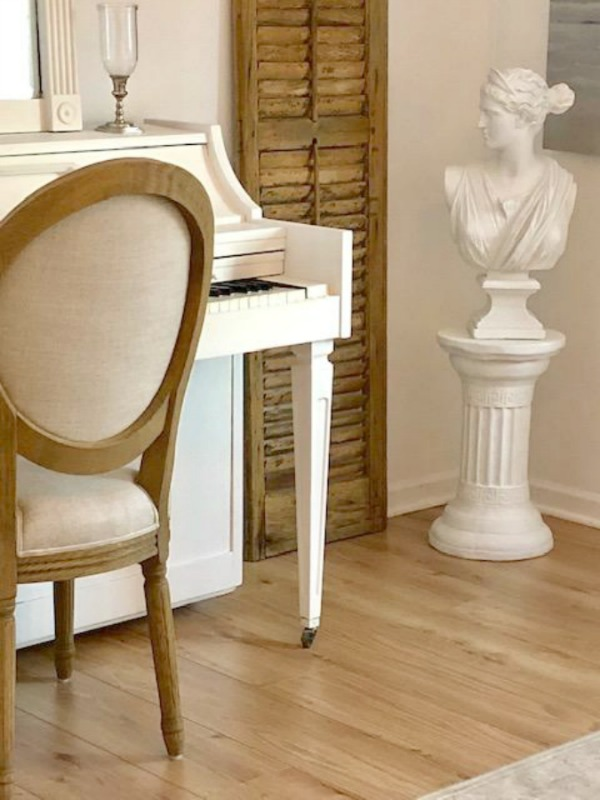 French farmhouse style and neutral palette in a studio with white piano, rustic shutter, and white bust of Diana. Piano is painted Benjamin Moore White Dove, and walls are Benjamin Moore White.