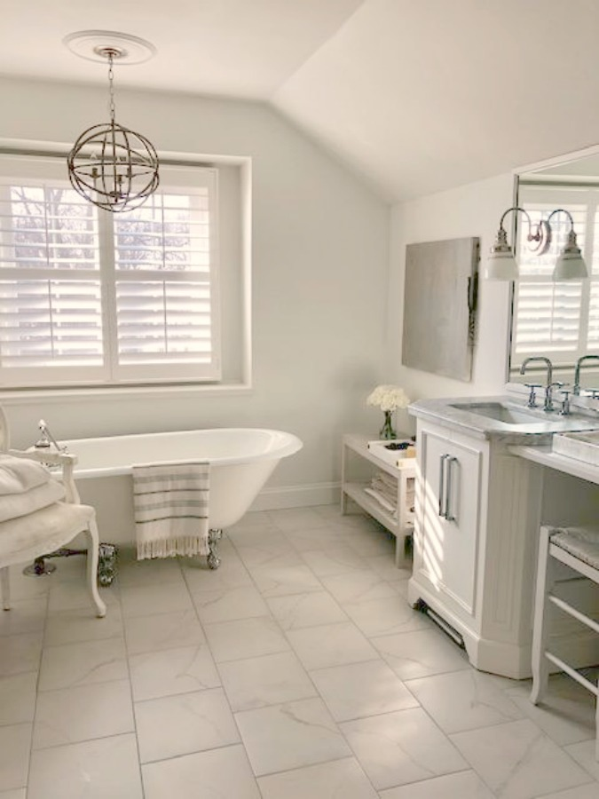 Classic white bathroom with vintage clawfoot tub, plantation shutters, abstract art, and staggered tile floor - Hello Lovely Studio.