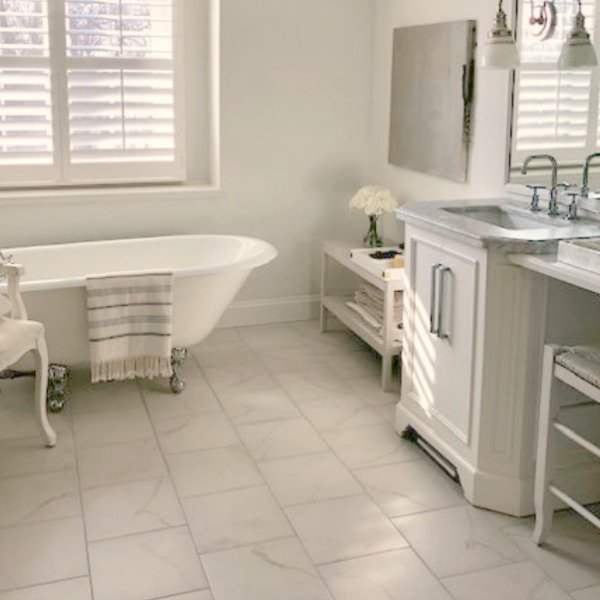 White bathroom with staggered porcelain tile floor and clawfoot tub - Hello Lovely Studio.