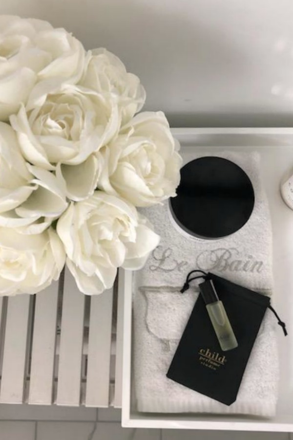 Black and white vignette with Child perfume and white roses in a bathroom by Hello Lovely Studio.