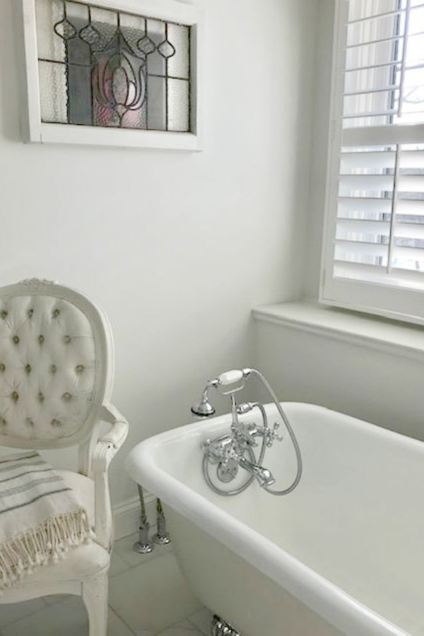 Romantic vintage style white bathroom with clawfoot tub and Louis French chair - Hello Lovely Studio.
