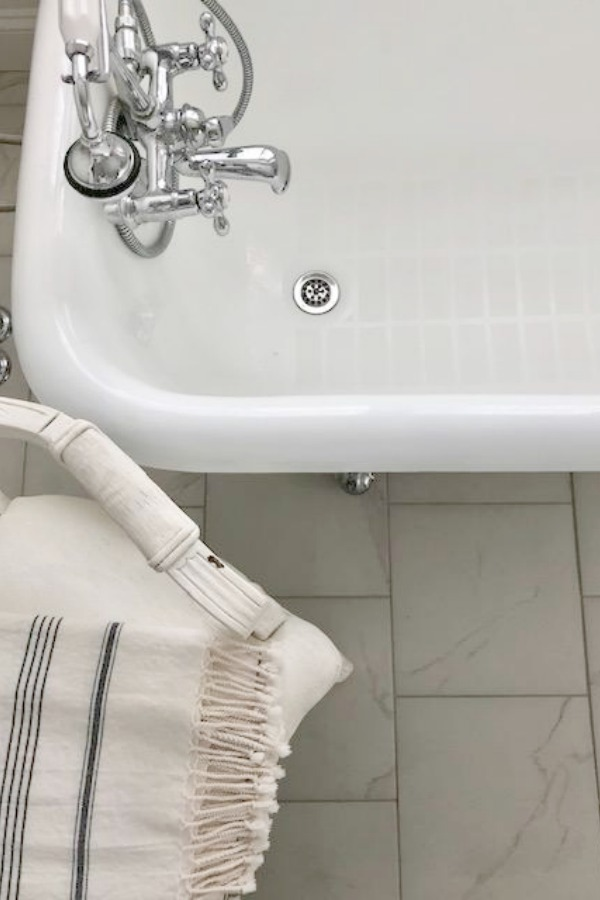 Detail of vintage clawfoot bathtub and porcelain tile floor - Hello Lovely Studio.