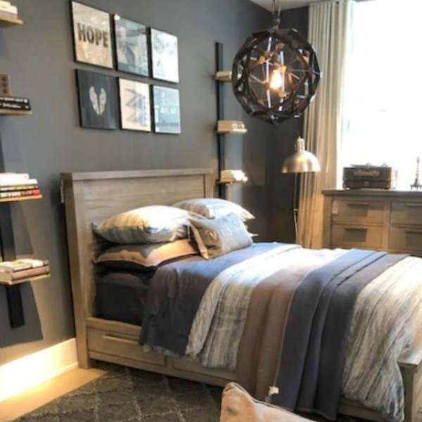 Masculine bedroom with dark grey wall and industrial farmhouse elements at RH Gallery Chicago. Photo: Hello Lovely Studio. Come tour photos of Restoration Hardware: Romantic French Decor Ideas on Hello Lovely Studio.