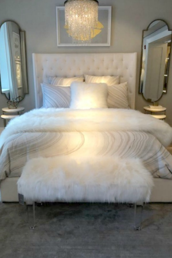Romantic and French inspired bedroom with tufted wing style headboard at RH Gallery Chicago. Photo: Hello Lovely Studio. Come tour photos of Restoration Hardware: Romantic French Decor Ideas on Hello Lovely Studio.