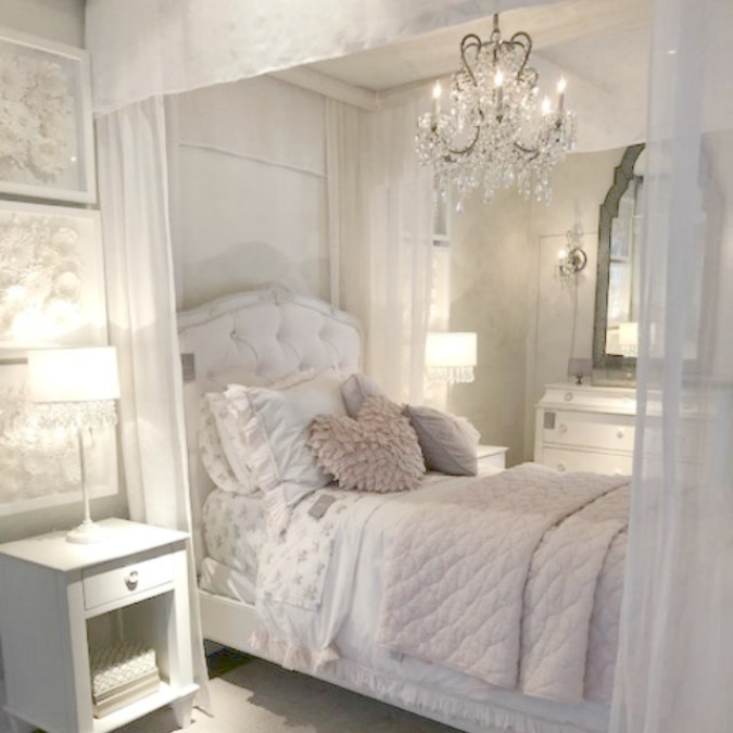 Gorgeous French romantic bedroom with canopy bed, crystal chandelier, pink bedding, and French country furniture. Come tour photos of Restoration Hardware: Romantic French Decor Ideas on Hello Lovely Studio.