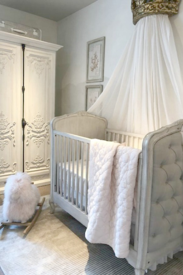 Beautiful French nursery with tufted linen upholstered crib, ornate armoire with cremone bolt, and sheepskin rocker - all by RH. Photo: Hello Lovely Studio. Come tour photos of Restoration Hardware: Romantic French Decor Ideas on Hello Lovely Studio.