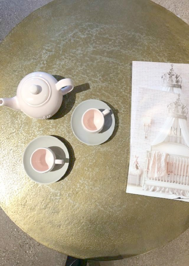 Pale pink tea set on a metallic round table at RH Gallery Chicago. Come tour photos of Restoration Hardware: Romantic French Decor Ideas on Hello Lovely Studio.