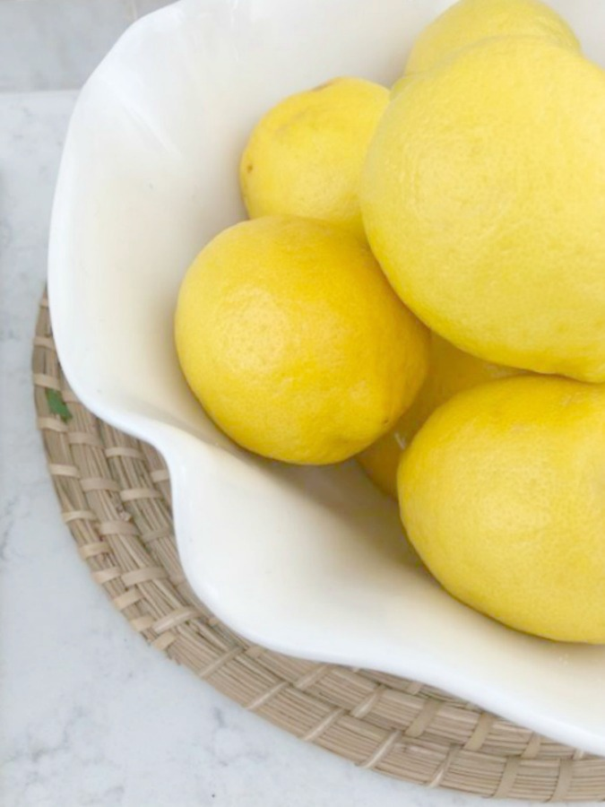 Beautiful vibrant yellow lemons in a scalloped white bowl on a round rattan charger. Hello Lovely Studio.