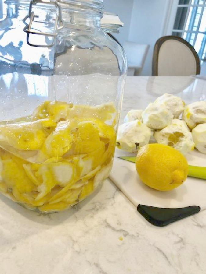 Lemon peels in jar with vodka for easy homemade limoncello recipe on Hello Lovely Studio.