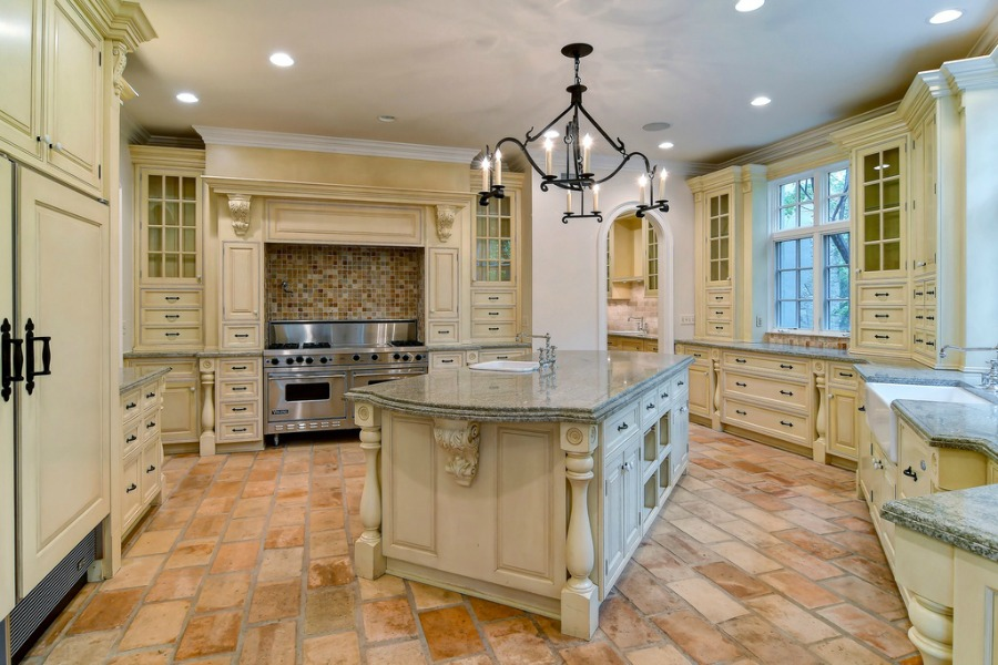 French country traditional style kitchen with rustic terracotta stone tile floor in a grand Hinsdale home.