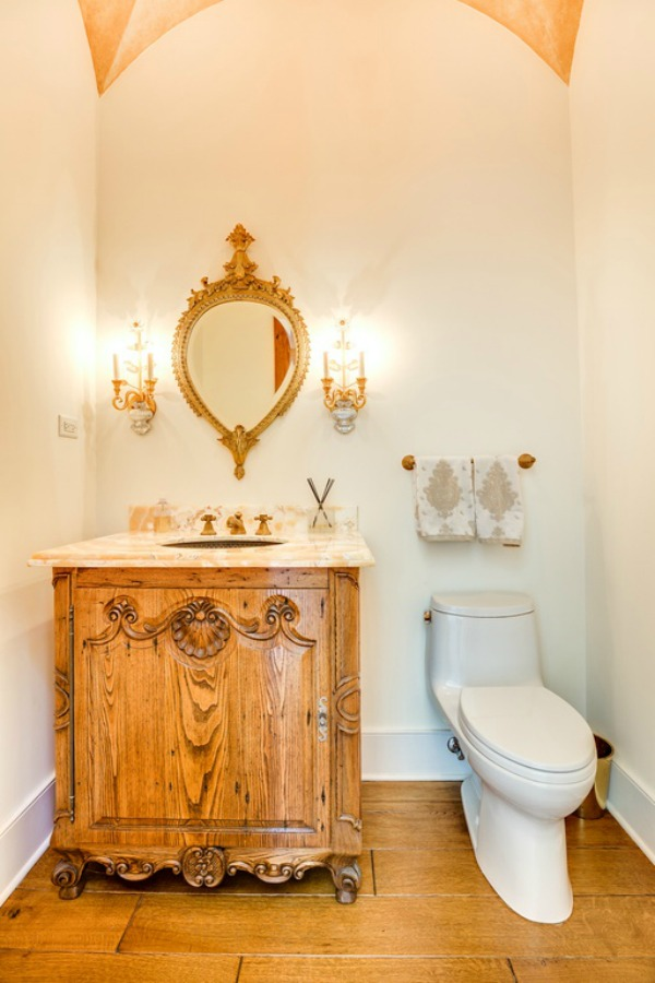 Charming powder room with French country design and a vintage style wood vanity.