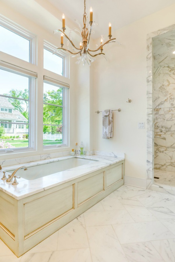 Painted wood bathtub apron in a luxurious white marble bathroom in a French country home. Come explore Realistic Country French Decor from Luxurious Ideas...certainly lovely indeed. Decorating ideas for French country style rooms as well as shopping resources.