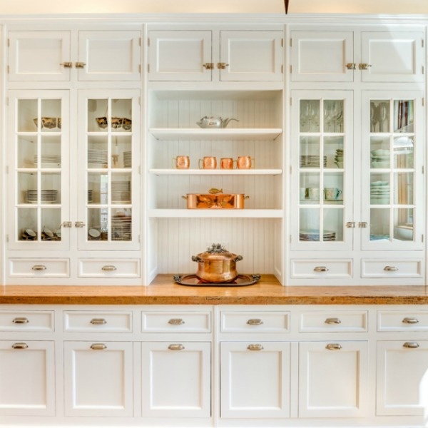 Magnificent custom white Shaker cabinetry in a French kitchen with wood countertops and copper accents. Located in Elmhurst IL.