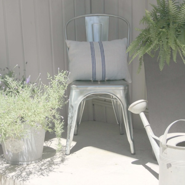 French Tolix style chair with grainsack pillow and farmhouse galvanized buckets on my front porch - Hello Lovely Studio.