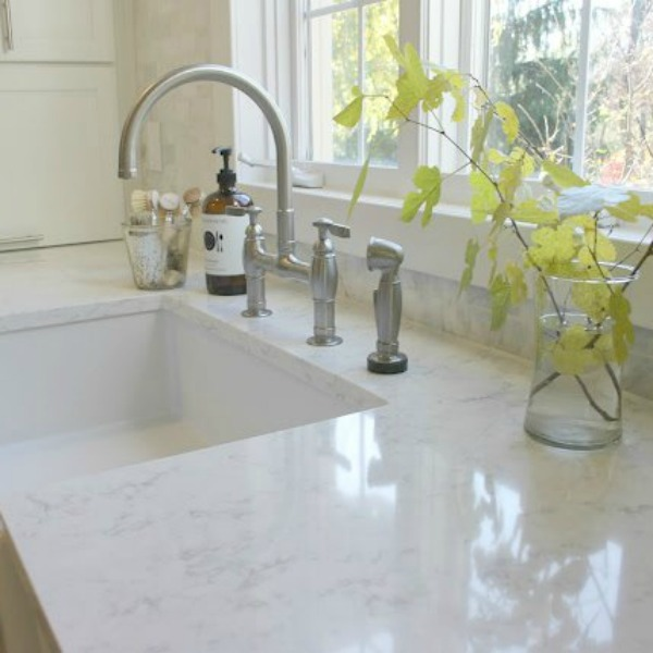My white classic kitchen with Viatera quartz countertops in Minuet, Kohler Park bridge faucet, and farm sink. Hello Lovely Studio.