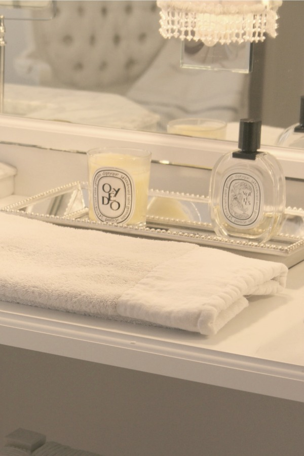 Mirrored tray with Diptyque essentials in our bathroom - Hello Lovely Studio. Come discover more inspiring trays for layering and vignettes in Adding Tray Très Chic to Your Home.