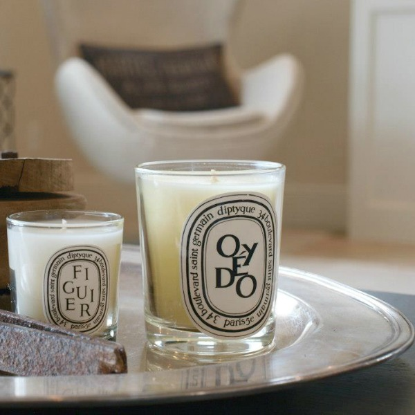 Diptyque candles upon a hotel silver oval tray in our living room - Hello Lovely Studio. Come discover more inspiring trays for layering and vignettes in Adding Tray Très Chic to Your Home.