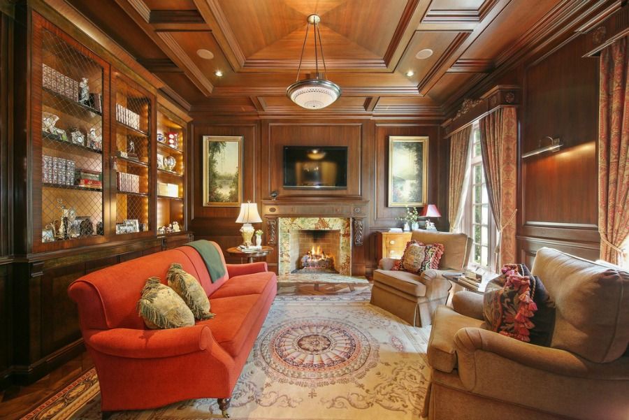 Handsome French Country den with fireplace and wood paneled walls.