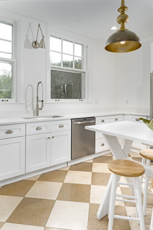 Modern French country kitchen with white Shaker cabinetry, checkerboard floor, and white orchard table with stools - Geneva, IL.
