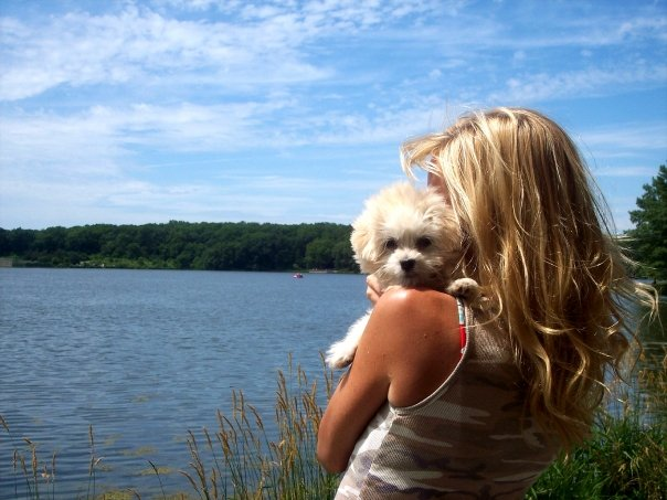 Michele of Hello Lovely Studio at lake with white puppy.