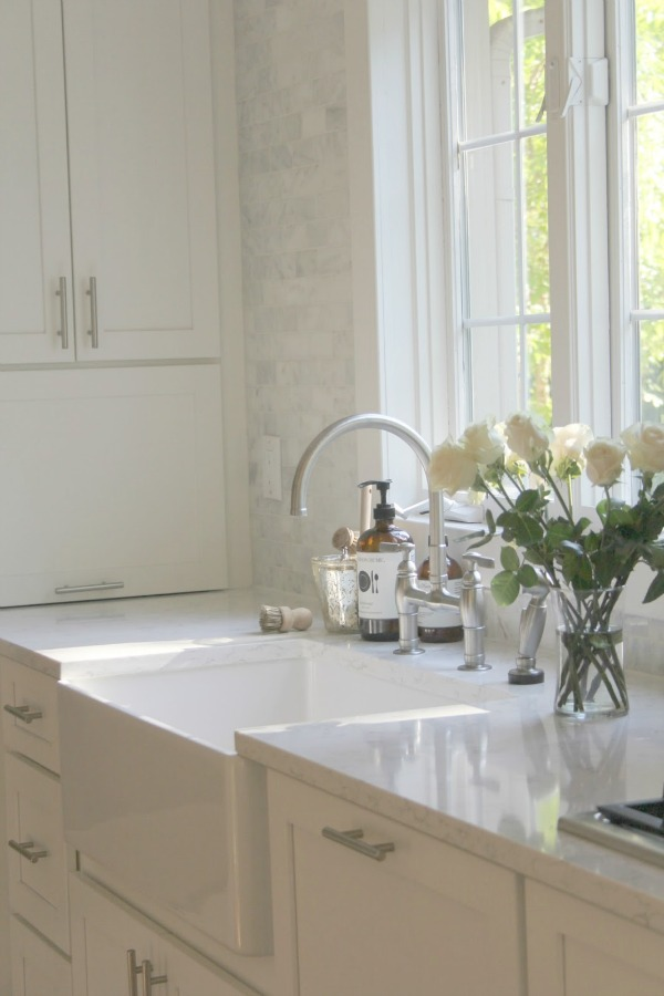 White kitchen by Hello Lovely Studio with farm sink and bridge faucet.