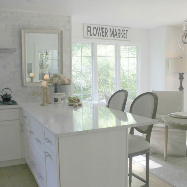 Serene white neutral kitchen with Viatera Minuet countertops, polished subway marble backsplash, and Belgian linen dining chairs. Hello Lovely Studio.