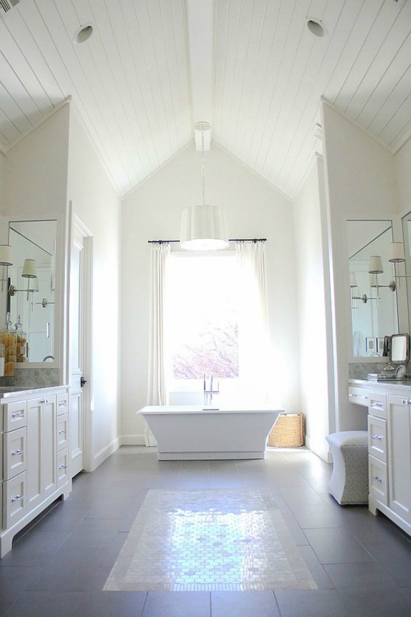 Luxurious and classic white bathroom with high ceiling, shiplap, freestanding tub, and walls painted Sherwin Williams Alabaster.