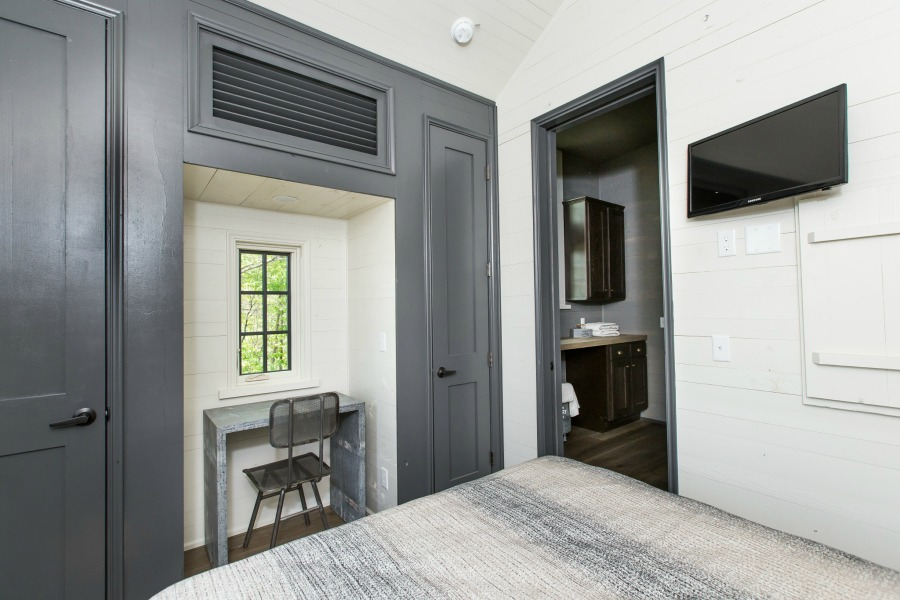 Built-in desk area flanked by closets in bedroom of tiny house designed by Jeffrey Dungan, an exquisitely crafted luxurious Low Country style Designer Cottage at The Retreat at Oakstone.