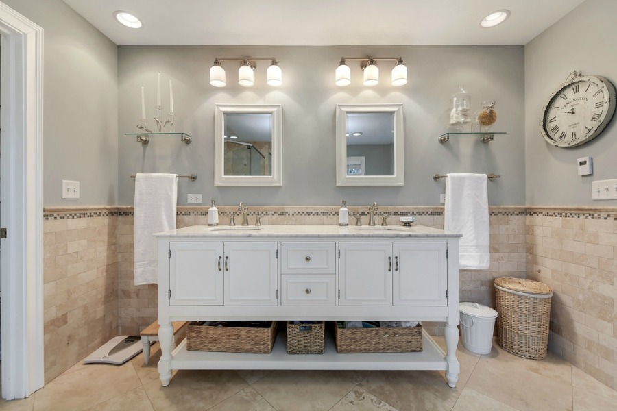 Traditional French country bathroom design with freestanding vanity and travertine tile in a grand home in Wheaton.