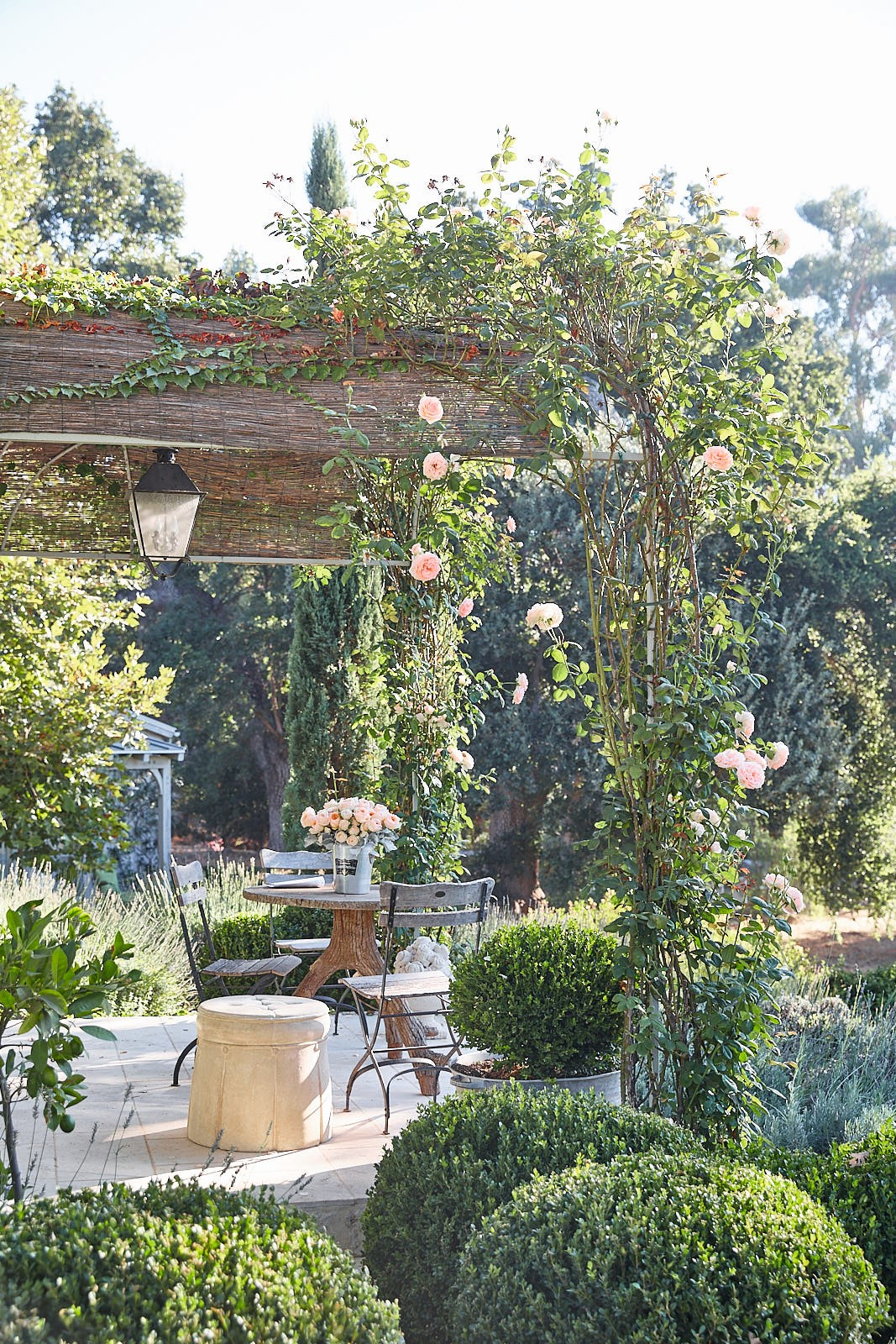 Patina Living photo of outdoor lush garden and patio with rustic modern farmhouse style at Patina Farm. Brooke Giannetti & Steve Giannetti designed the beautiful property. Photo by Victora Pearson.