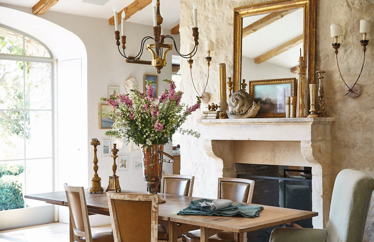 Patina Living photo of dining room with limestone French mantel, French farmhouse chandeliers, plaster walls, and rustic modern farmhouse style. Brooke Giannetti and Steve Giannetti designed the space at Patina Farm. Photo by Victoria Pearson.