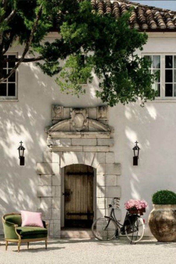 Montrose guest house at home in Houston with white stucco and exquisite reclaimed stone at entry with rustic door. Come enjoy photos of this house tour with architecture by Reagan Andre.