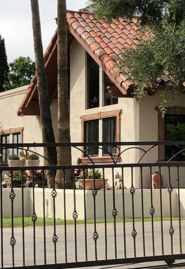 Beautiful house exterior with wrought iron gate - Hello Lovely Studio.